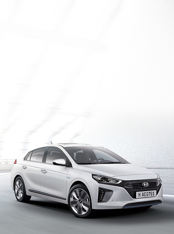White Ioniq Hybrid is driving on the road next to an ocean